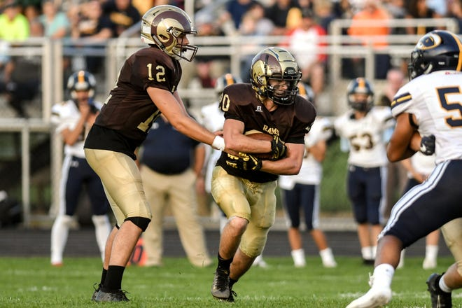 Holt's Logan VanEnkevort, right, takes the handoff from quarterback Nick Johnson during the first quarter on Friday, Sept. 20, 2019, in Holt.