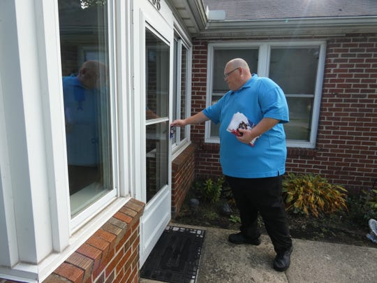 Kevin Norris, a Republican running for mayor, leaves campaign literature at a house on Forest Lawn Boulevard while going door-to-door campaigning on a recent Saturday.