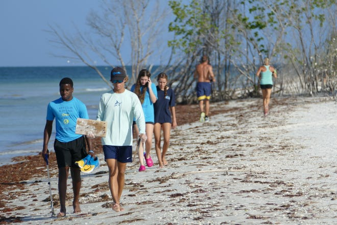 Landon McLain (right) from Marco Island Academy carries a piece of wood, attached nails included, during the International Coastal Cleanup in Tigertail Beach in Marco Island on Sept. 21, 2019. Other classmates walk with him and, in the background, a man and a woman jog in opposite direction.