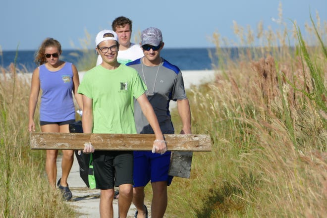 Teens carry pieces of wood during the International Coastal Cleanup in Tigertail Beach in Marco Island on Sept. 21, 2019.