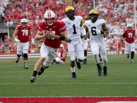Badgers quarterback Jack Coan (17) gets past Michigan's Ambry Thomas and Josh Uche for a rushing touchdown late in the first half Saturday.