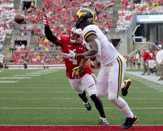 Badgers cornerback Donte Burton attempts to knock the ball away from intended receiver Tarik Black of Michigan during the second half.