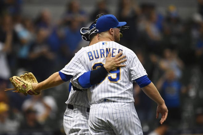 The Brewers' Corbin Burnes is congratulated by catcher Manny Pina after pitching a hitless ninth inning against the Pirates on Friday night.
