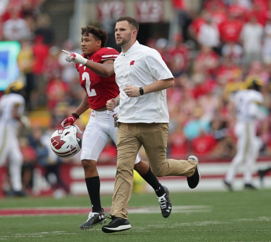 Wisconsin safety Reggie Pearson is escorted off the field after a ejection for targeting during the second half Saturday.