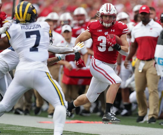 Badgers running back Garrett Groshek finds room along the sideline against Michigan's defense for a nice gain during the first half Saturday.