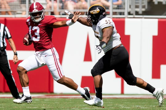 Alabama quarterback Tua Tagovailoa (13) carries for a gain against Southern Miss defensive lineman Demarrio Smith (55) at Bryant-Denny Stadium in Tuscaloosa, Ala., on Saturday September 21, 2019.