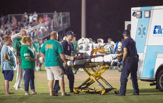 Hooper Academy's Grant Tyson is attended to after being injured during a play early in the second quarter against Lowndes Academy.