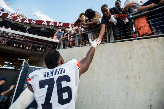 Auburn offensive lineman Prince Tega Wanogho (76) high fives fans after the game at Kyle Field in College Station, Texas, on Saturday, Sept. 21, 2019. Auburn defeated Texas A&M 28-20.