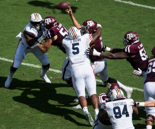 Texas A&M quarterback Kellen Mond (11) gets the ball off as he is hit by Auburn defensive lineman Derrick Brown (5) at Kyle Field in College Station, Texas, on Saturday, Sept. 21, 2019.