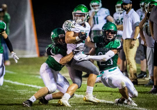 FILE -- A pair of Yorktown defenders makes a tackle against New Castle during their game at Yorktown High School Friday, Sept. 20, 2019.