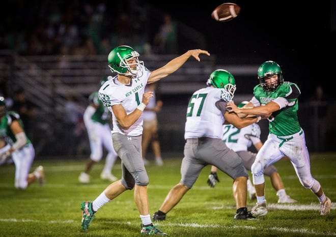 FILE -- New Castle quarterback William Grieser attempts a pass during the Trojans' game Sept. 20 against Yorktown at Yorktown High School.