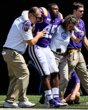 LSU linebacker Michael Divinity Jr. (45) is helped off the field after an injury during the first half against Vanderbilt at Vanderbilt Stadium in Nashville, Tenn., Saturday, Sept. 21, 2019.