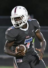 First Baptist Academy football quarterback Rich Mellien runs the ball against Community School of Naples during their Military and First responders appreciation game night on Friday. Mellien, who replaced Brady Dean after he transferred to St. Thomas Aquinas in March, threw five touchdown passes and ran for another.