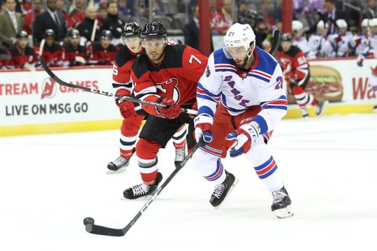 New York Rangers left wing Phillip Di Giuseppe (28) controls the puck next to New Jersey Devils defenseman Matt Tennyson (7) during the first period of a preseason NHL hockey game Friday, Sept. 20, 2019, in Newark, N.J.