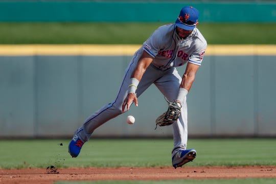 New York Mets shortstop Amed Rosario bobbles the ball after third baseman Todd Frazier commited an error on a fielder's choice hit by Cincinnati Reds' Eugenio Suarez off starting pitcher Zack Wheeler in the first inning of a baseball game, Saturday, Sept. 21, 2019, in Cincinnati.