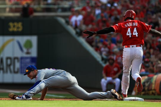 Sep 21, 2019; Cincinnati, OH, USA; Cincinnati Reds right fielder Aristides Aquino (44) reacts to hitting an RBI single as New York Mets first baseman Pete Alonso (20) attempts to keep his foot on the base in the first inning at Great American Ball Park.