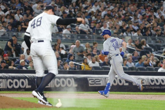 Toronto Blue Jays first baseman Justin Smoak (14) rounds the bases after hitting a two run home run against New York Yankees relief pitcher Tommy Kahnle (48) during the seventh inning at Yankee Stadium.