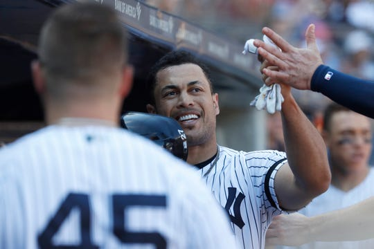 New York Yankees' Giancarlo Stanton celebrates with teammates after scoring off a single hit by teammate Mike Ford against the Toronto Blue Jays during the fourth inning of the team's Major League baseball game, Saturday, Sept. 21, 2019, in New York.