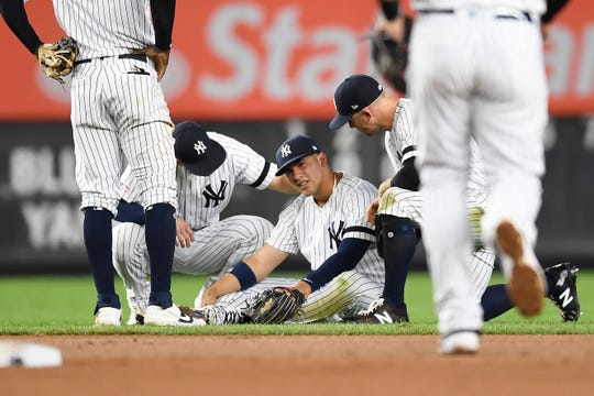 New York Yankees second baseman Gleyber Torres sits on the ground after slipping while trying to field a ground ball during the fourth inning of the team's baseball game against the Toronto Blue Jays, Friday, Sept. 20, 2019, in New York.