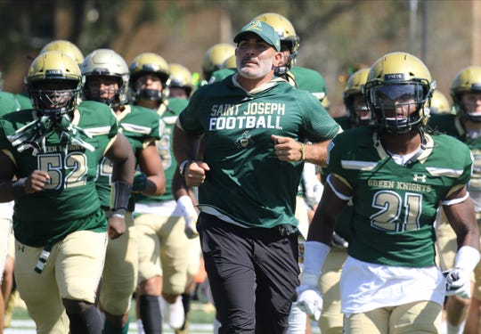 St. Joseph head coach Augie Hoffmann takes the field with his team to start the game against DePaul in Monntvale on September 21, 2019.