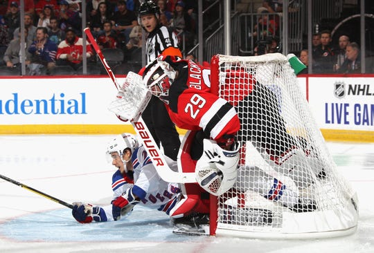 Brett Howden #21 of the New York Rangers slides into Mackenzie Blackwood #29 of the New Jersey Devils during the first period at the Prudential Center on September 20, 2019 in Newark, New Jersey.