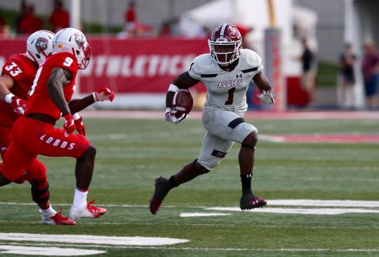 New Mexico State running back Jason Huntley looks for running room on Saturday against the University of New Mexico.