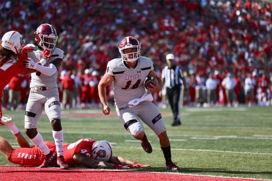 New Mexico State quarterback Josh Adkins scores a rushing touchdown in the first half of Saturday's football game at the University of New Mexico.