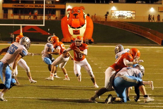 Artesia's Clay Houghtaling scrambles for yardage in the final minute of the first half against Cleveland.