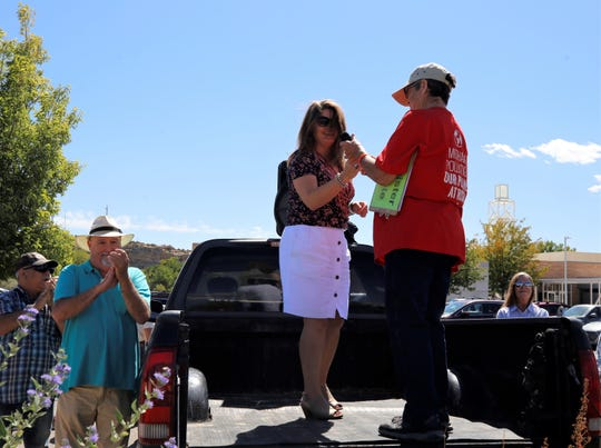 Maggie Toulouse Oliver accepts the microphone from San Juan County Democratic Party Chairwoman MP Schildmeyer, Friday, Sept. 20, 2019, during the Global Climate Strike at Gateway Park in Farmington.