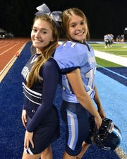 Twins Jenna, left, and Maya Millis both contributed to the Livonia Stevenson High football game on Sept. 20. Jenna as a varsity sideline cheerleader and Maya as the football team's extra point kicker.