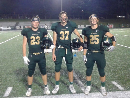 Howell players Bryan Greene, Daniel Honkala and Jonah Schrock pose after their victory over Novi on September 20, 2019.