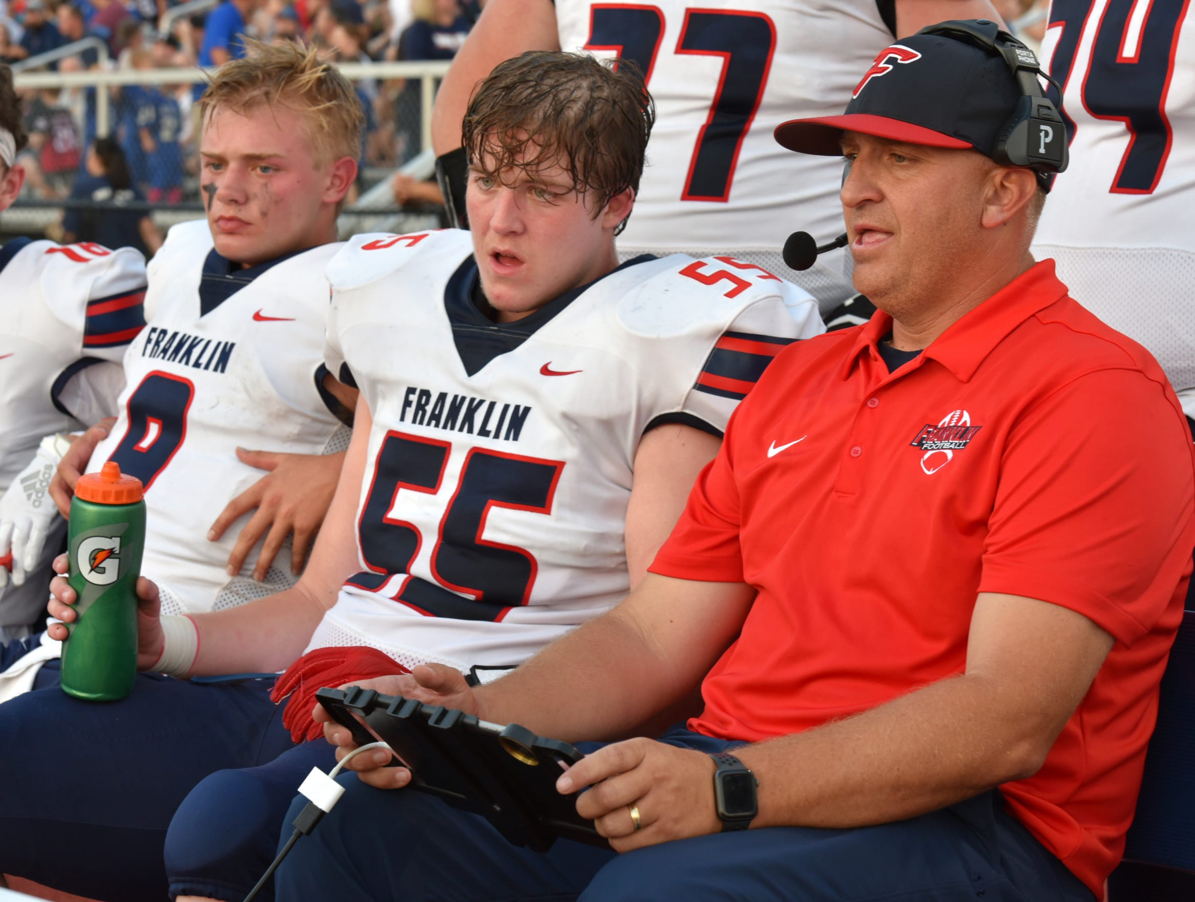 Jacob Kelbert, far left, sits with his father - Franklin Patriot coach Chis Kelbert, right, and Seth Winter, (#55) on Sept. 20 as the offense goes over a play early in the game.