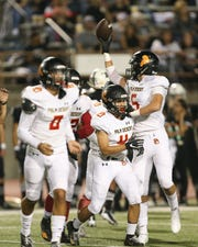 Cole Martello (with ball) and the Aztecs defense celebrate a fumble recovery on Friday against Permian in Odessa, Texas.