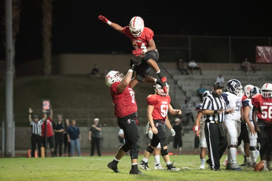 Palm Springs' Julian Polendo lifts teammate Jason Roberts after Roberts scored a touchdown during the game against Redlands in Palm Springs, Calif., on Friday, September 20, 2019.