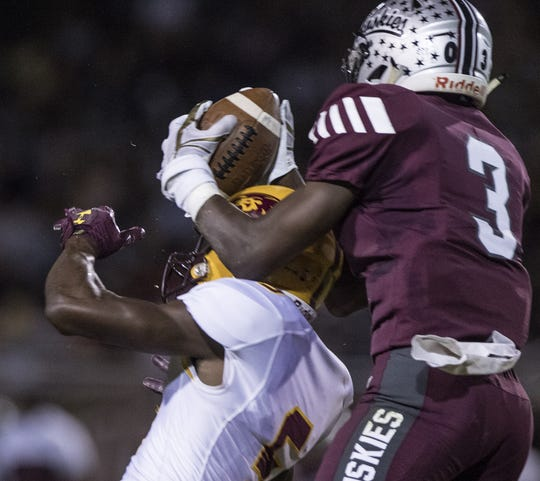 Hamilton's Zachary Lewis (3) gets an interception off of  Mountain Pointe's Dominique Davis (5) helmet during the first half of their game in Chandler, Friday, Sept. 20, 2019.