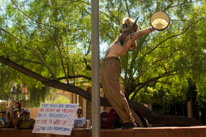 Jake Angeli, shamanic practitioner, leads the crowd in a yell before the march in solidarity with climate activism groups across the country to the Arizona State Capitol Building Friday, September 20, 2019.