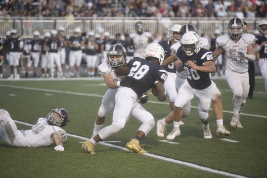Chambersburg running back Keyshawn Jones breaks through tackles on Friday, September 20 against State College at Trojan Stadium.