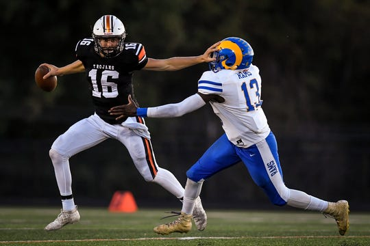 York Suburban quarterback Max Reinecker stiff arms Kennard-Dale defensive end JJ Kennedy to break away for a pass attempt, Friday, September 20, 2019.