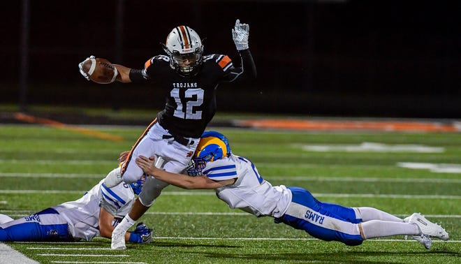 York Suburban wideout David Moye avoids tackles by Josh Vipperman, left, and Steven Lukes of Kennard-Dale, Friday, Septmber 20, 2019.