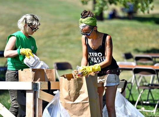 Owner Jade Garcia, right, and Anya Sharif, both of Unified Earth Vision, a nonprofit based in Freeland, Md., sort through waste during Harvest Vegfest at Cousler Park in Manchester Township, Saturday, Sept. 21, 2019. Dawn J. Sagert photo