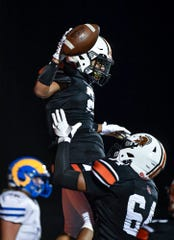 Devante Banks, seen here lifting up teammate Savion Harrison, was selected a second-team all-state offensive lineman in Class 4-A by the Pennsylvania Football News. Harrison was a first-team pick at running back.