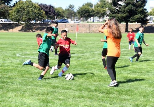 Los niños disfrutan de un partido de futbol soccer en la inauguración del Complejo de Fútbol en Constitution Blvd.