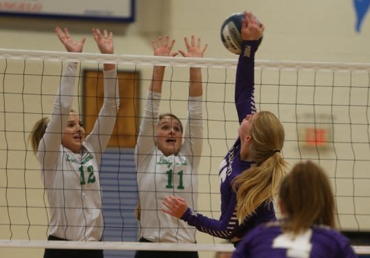 Lauren Scherr, far left, and Kylie Phillips, center, prepare to block a shot for Wall during an early season tournament in this August 16, 2019 photo.