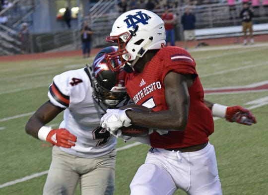 North DeSoto's David Atkins tries to get past Many's Jacolby Cade Friday night in Stonewall.