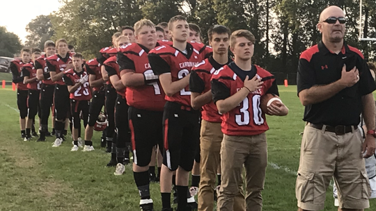 Dell Rapids St. Mary players and head coach Ross Flemmer during the National Anthem before the game against Avon on Friday, Sept. 20 in Dell Rapids.