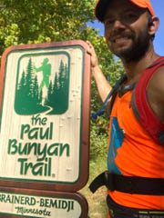 Chad Mickelson poses with a trail sign during his run across Minnesota.