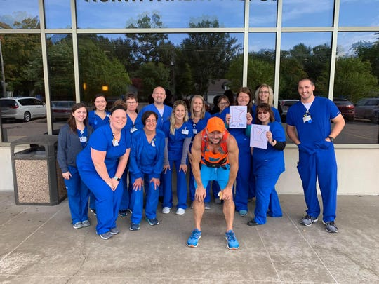 Chad Mickelson poses for a photo with co-workers at the St. Cloud Hospital during a run. Mickelson is running diagonally across the state and sharing his story of multiple sclerosis.