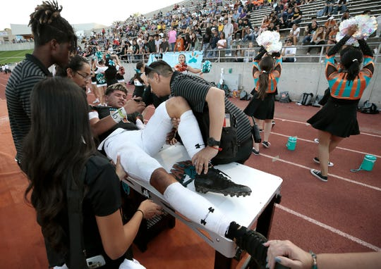 Pebble Hills quarterback Sebastian Ochoa is tended to after hurting his knee on a fourth-and-two keeper Friday night against San Angelo Central.