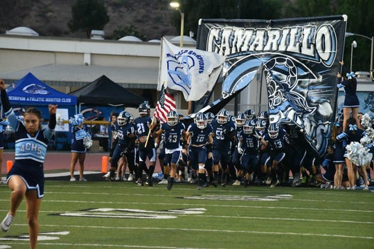The Camarillo High football enters the field before Friday night's game against Ventura at Moorpark College.