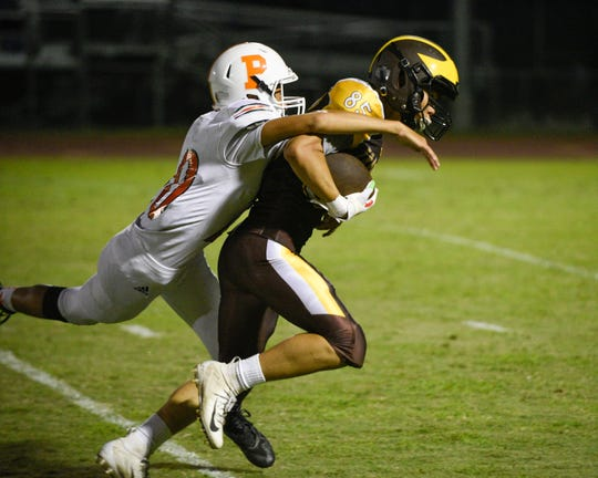 Golden West's Devin Hom gains yards after a reception setting up a touchdown against Porterville in a non-league high school football game at Visalia Community Stadium on Friday, Sept. 20, 2019.